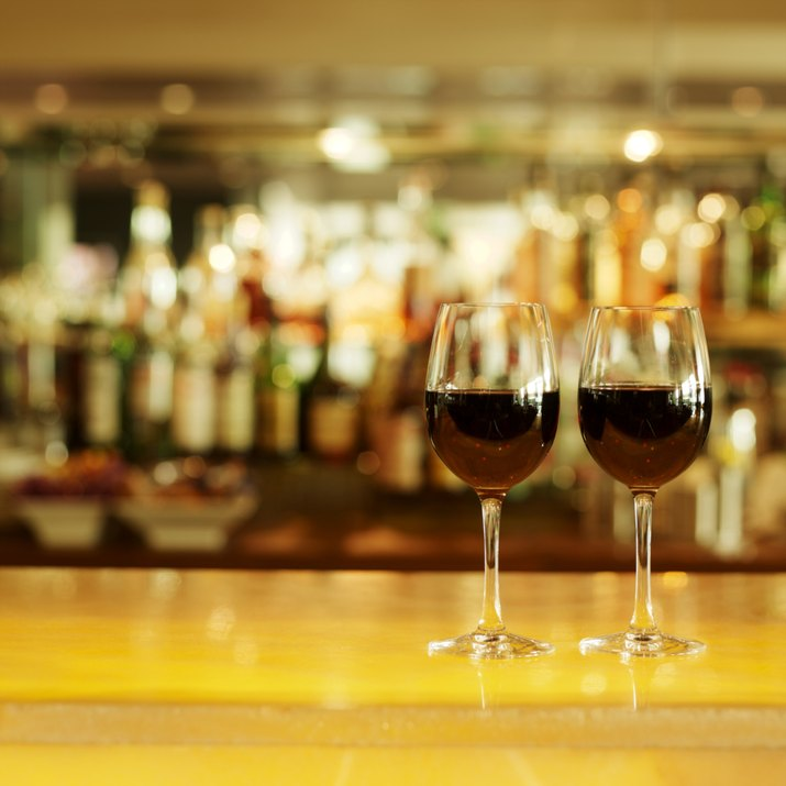 Close-up of two glasses of red wine on bar counter