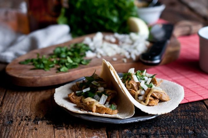 Two beer braised chicken tacos garnished with cilantro and diced onions.