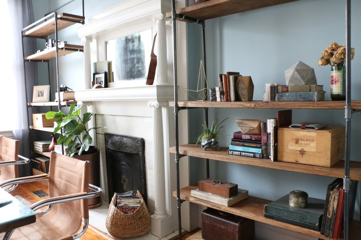 matching industrial pipe bookcases flanking a fireplace