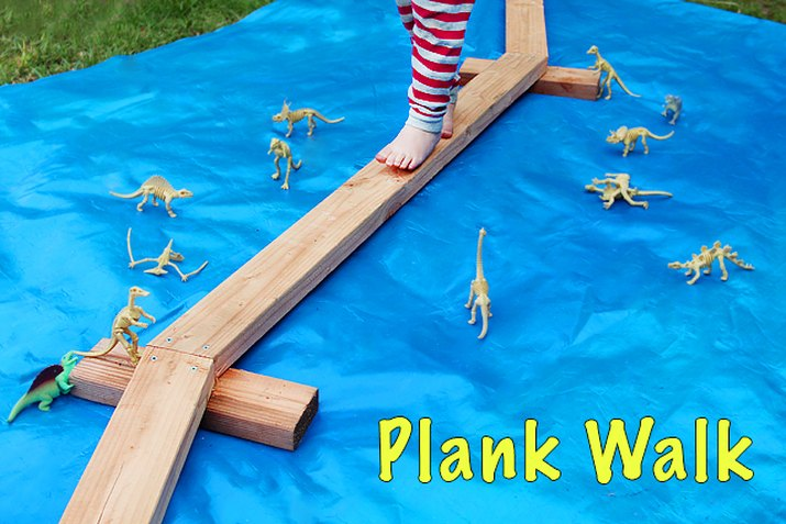 a child balancing on wooden planks laid on top of blue tarp