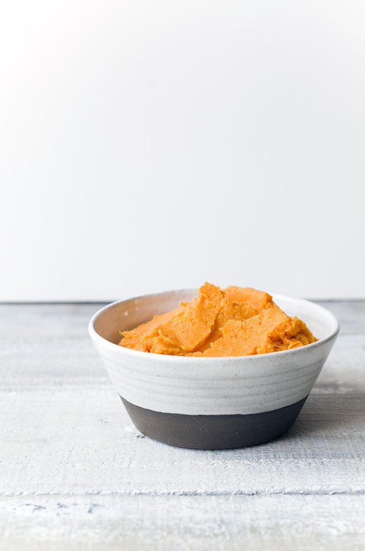 A bowl of creamy, orange mashed sweet potatoes.
