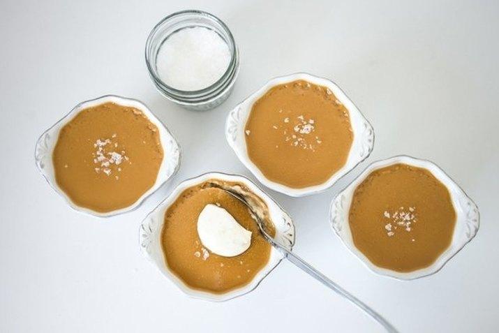 Four white ramekins filled with butterscotch pots de creme.
