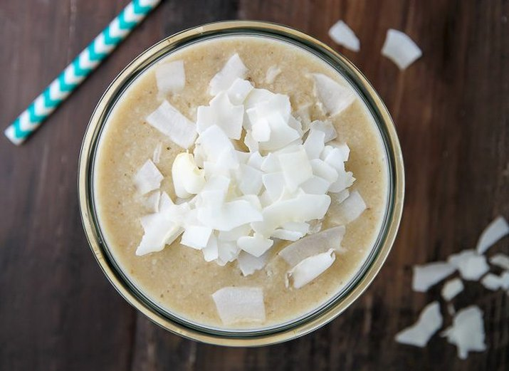 A jar of coconut cream pie smoothie topped with dried coconut flakes.