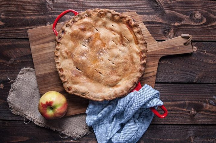 An apple pie baked in a cast iron skillet on a wood background