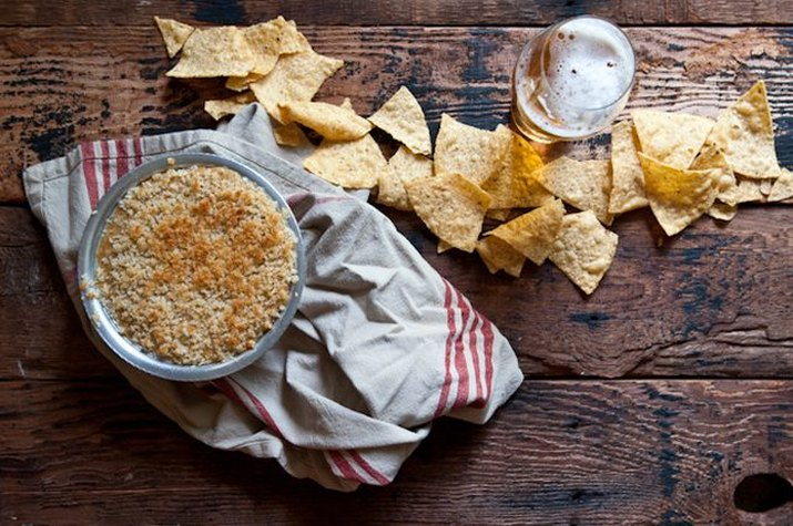 A freshly baked batch of jalapeno popper beer cheese dip served with tortillas.