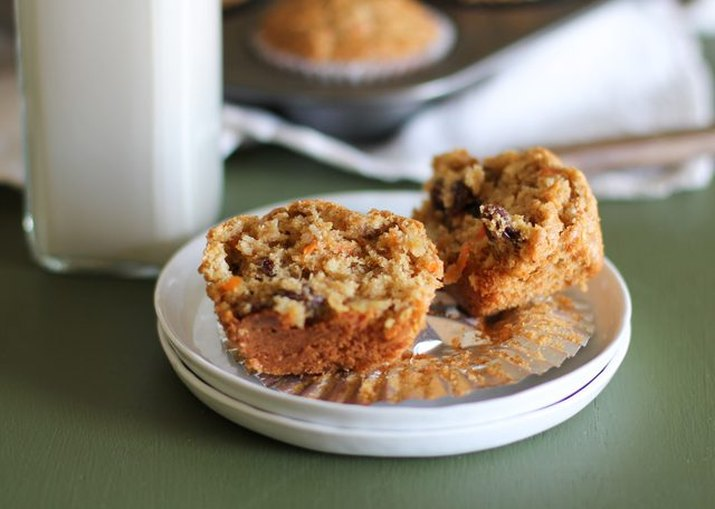 Jar of milk and a morning glory muffin cut open on plate.
