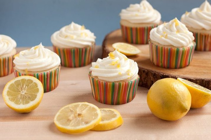 Lemon cupcakes topped with frosting, candies and fresh lemon zest.