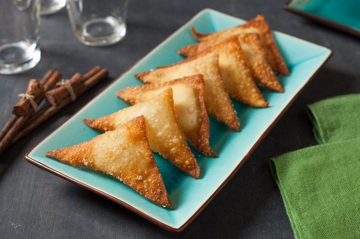 Golden brown cream cheese wontons stacked together on a plate.