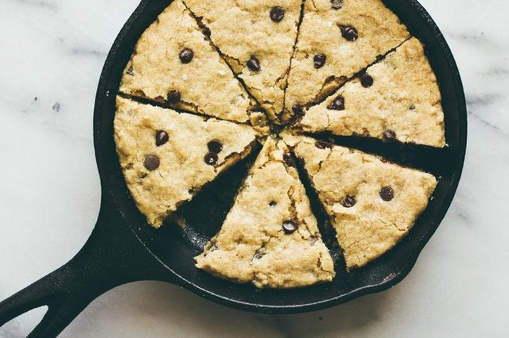A black cast iron skilled with a giant cookie cooked on it