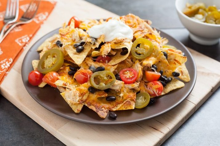 A plate of shredded chicken, jalapenos, tomatoes, black beans and sour cream on a bed of tortilla chips