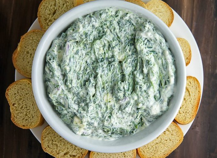 A bowl of creamy Greek yogurt spinach dip served with baguette slices.