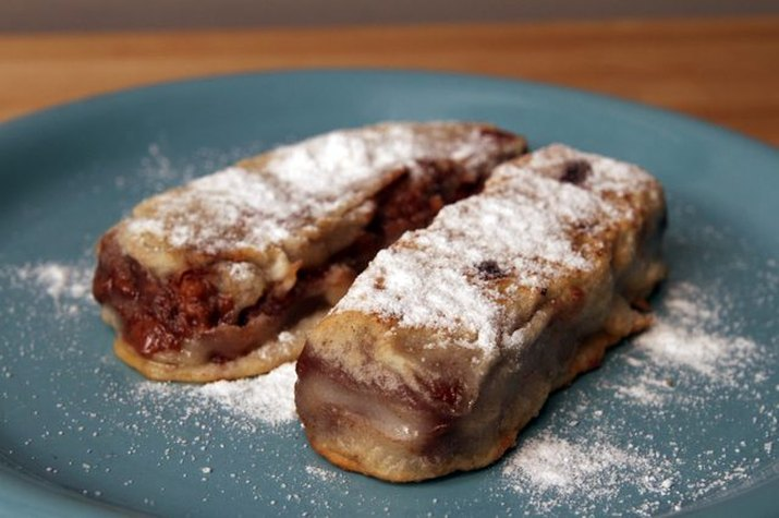Two deep fried Snickers sprinkled with powdered sugar.