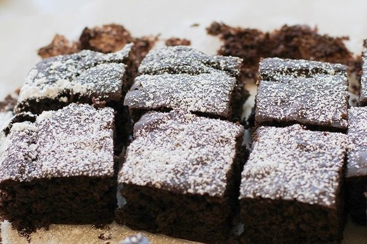 Dense black bean fudge brownie squares dusted with confectioner's sugar.