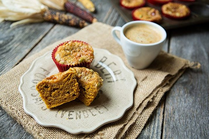 Spongey pumpkin spice latte muffins served with a hot coffee drink.