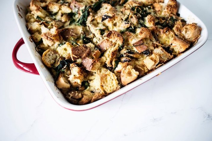 A strata with bread and spinach on a marble counter