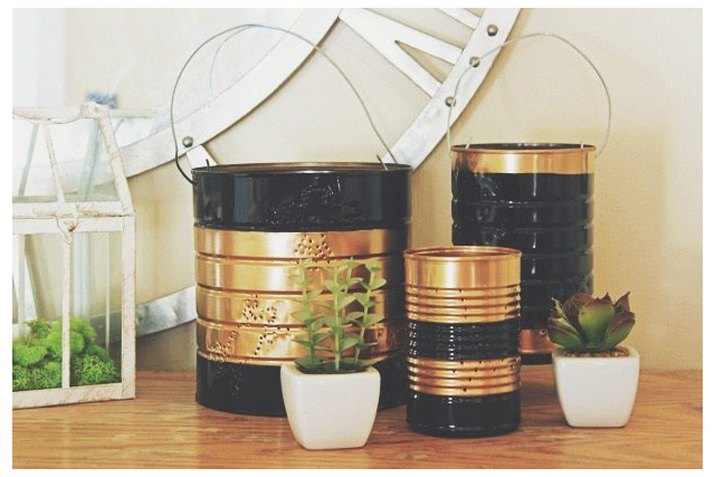 black and gold tin can lanterns on a shelf