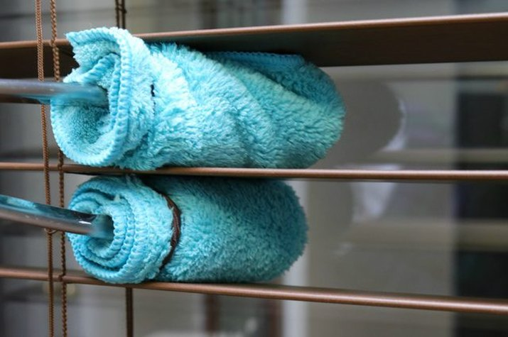 Metal tongs wrapped in microfiber cloth cleaning between wood blinds