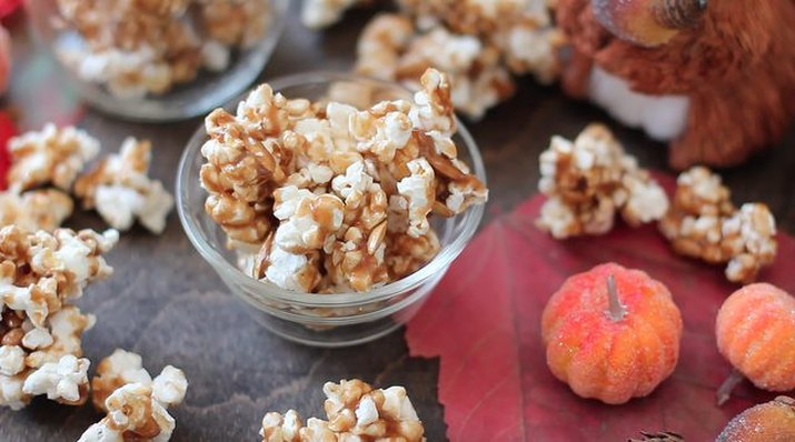 A bowl of pumpkin caramel corn surrounded by small pumpkins