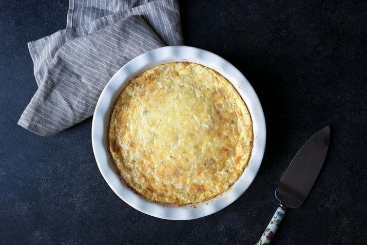 A crustless quiche in a white pie plate on a black background