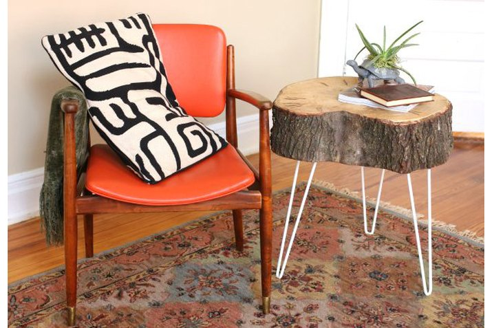 tree stump end table arranged with a chair and throw pillow