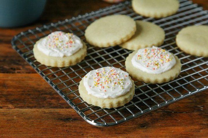 A batch of ready-made vegan sugar cookies decorated with buttercream frosting and sprinkles.