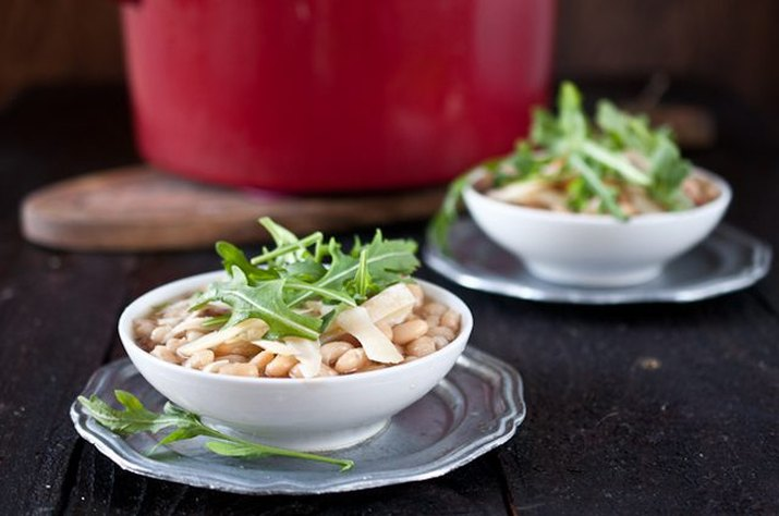 Slow cooker white bean beer and ham soup served with arugula