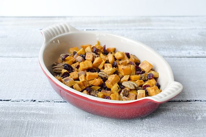 A dish filled with roasted sweet potatoes, cranberries and pecans.