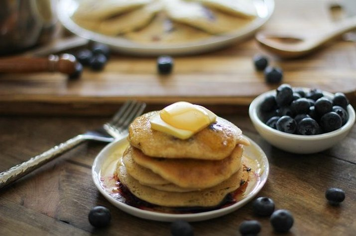 A stack of blueberry pancakes with butter and maple syrup.