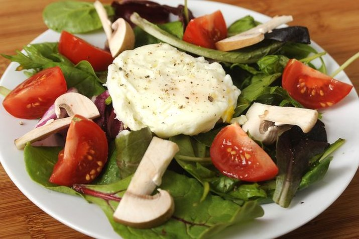 A seasoned poached egg served on top of a bed of salad.