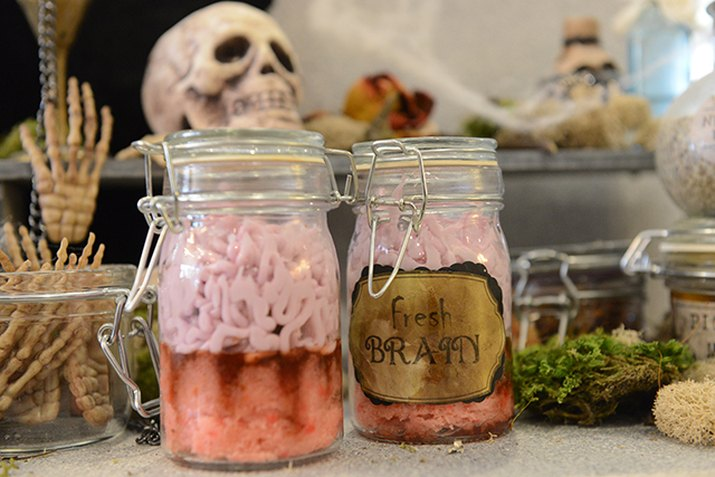Mason jar filled with cupcake and frosting so it looks like brains.