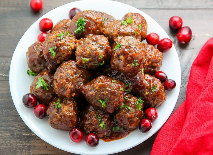 A pile of freshly baked cranberry meatballs decorated with whole cranberries.