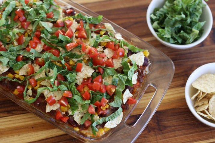 Taco casserole served with tortilla chips and extra garnish