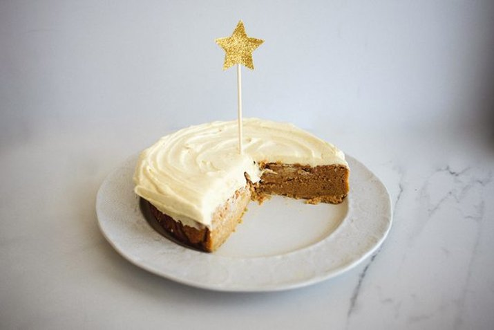 A pumpkin pie magic cake on a white plate with a quarter missing