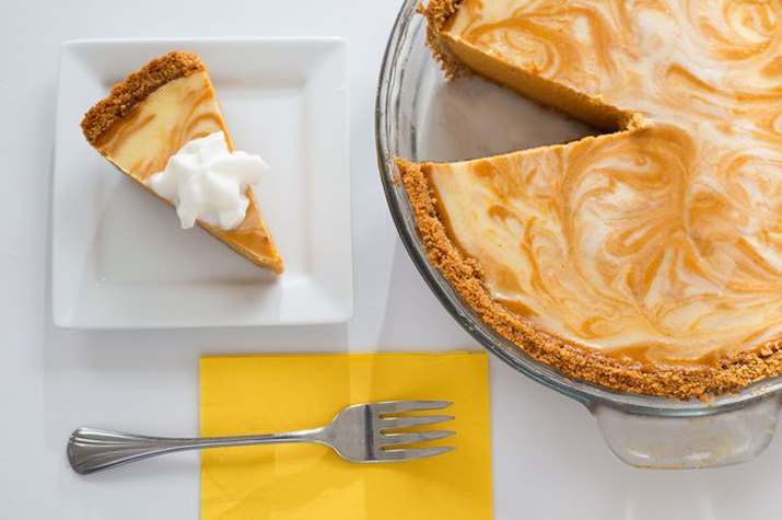 A swirly pumpkin cheesecake with whipped cream on top.