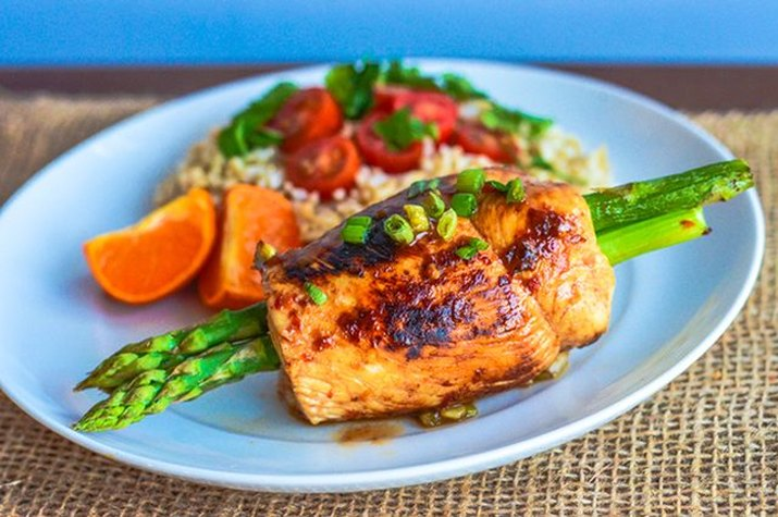 A plate of chicken-wrapped asparagus with rice, tomatoes and fruit.