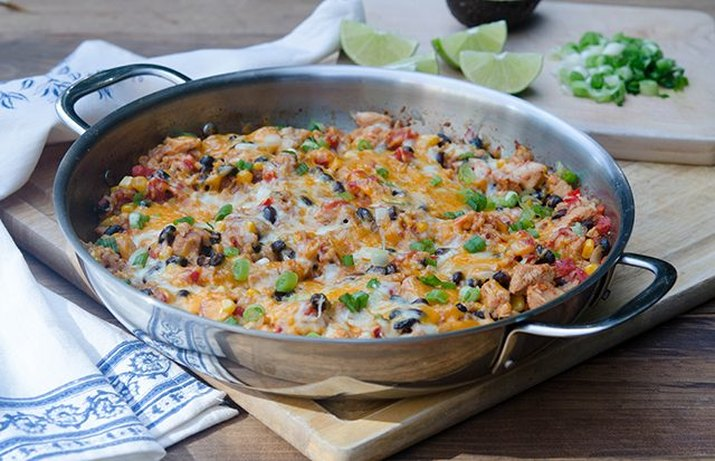 A colorful pot of Tex-Mex chicken and rice sprinkled with fresh cheese.