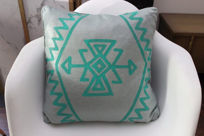 painted kilim pillow in a chair