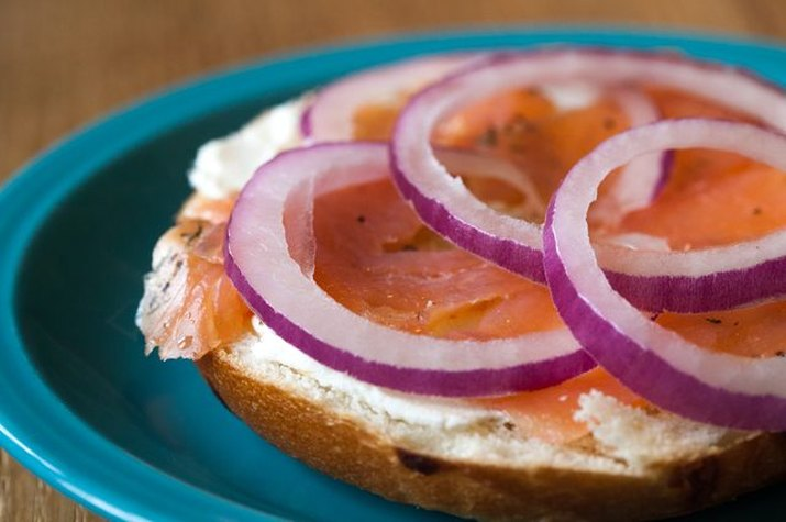 A half of a bagel topped with cream cheese, smoked salmon and red onion on a blue plate