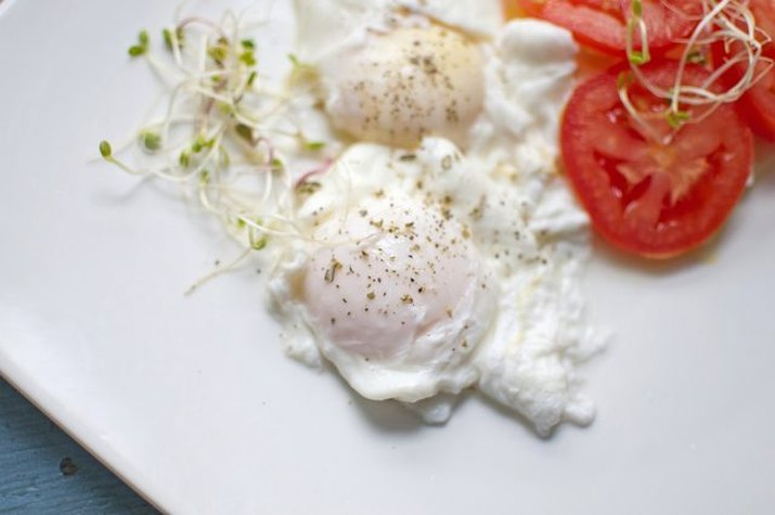 Two neatly poached eggs served with tomatoes.
