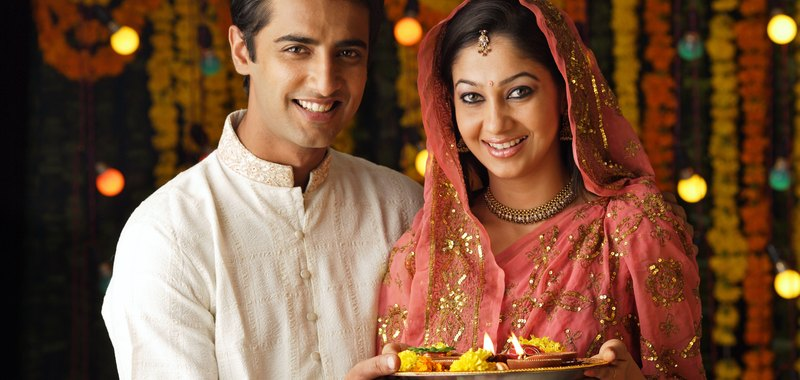 Portrait of a man and woman holding a pooja thali